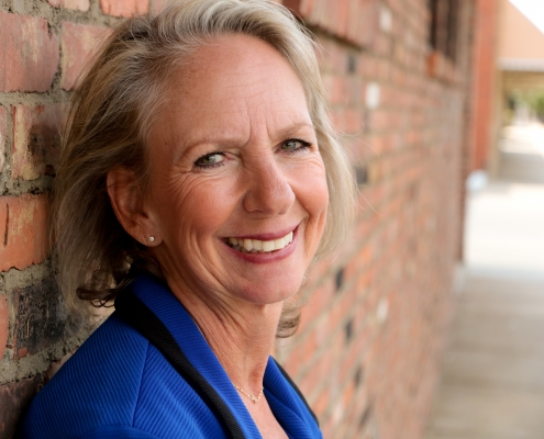 Cleveland DUI and Family Law Attorney Sherry Pidala smiles and leans against brick wall for headshot picture
