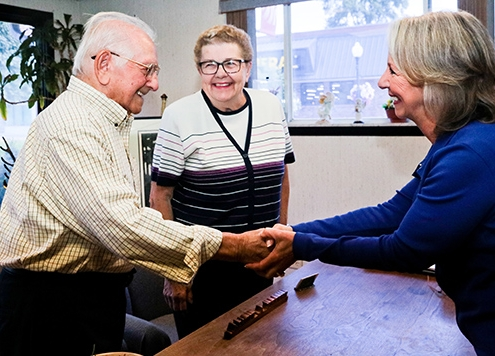 An elderly gentleman and his wife smile and shake hands with Attorney Sherry Pidala in her Bedford Heights law office where she represents clients from Cuyahoga, Summit, and Portage counties in Ohio