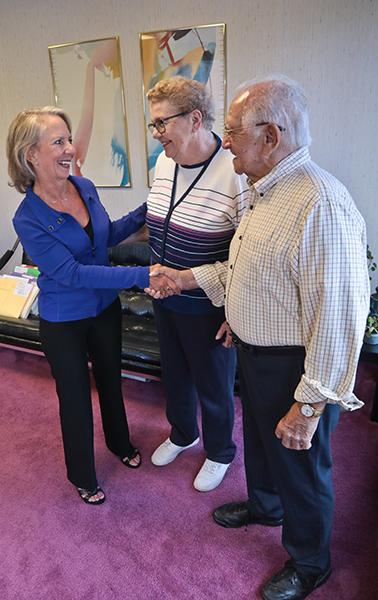 Estate Planning and Probate lawyer Sherry Pidala stands and shakes hands with elderly man and his wife smiles by his side looking at attorney Pidala in Cleveland Ohio